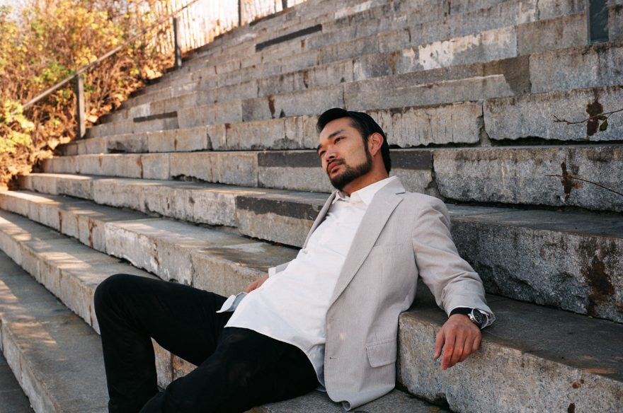 Asian guy sitting on steps in a white jacket