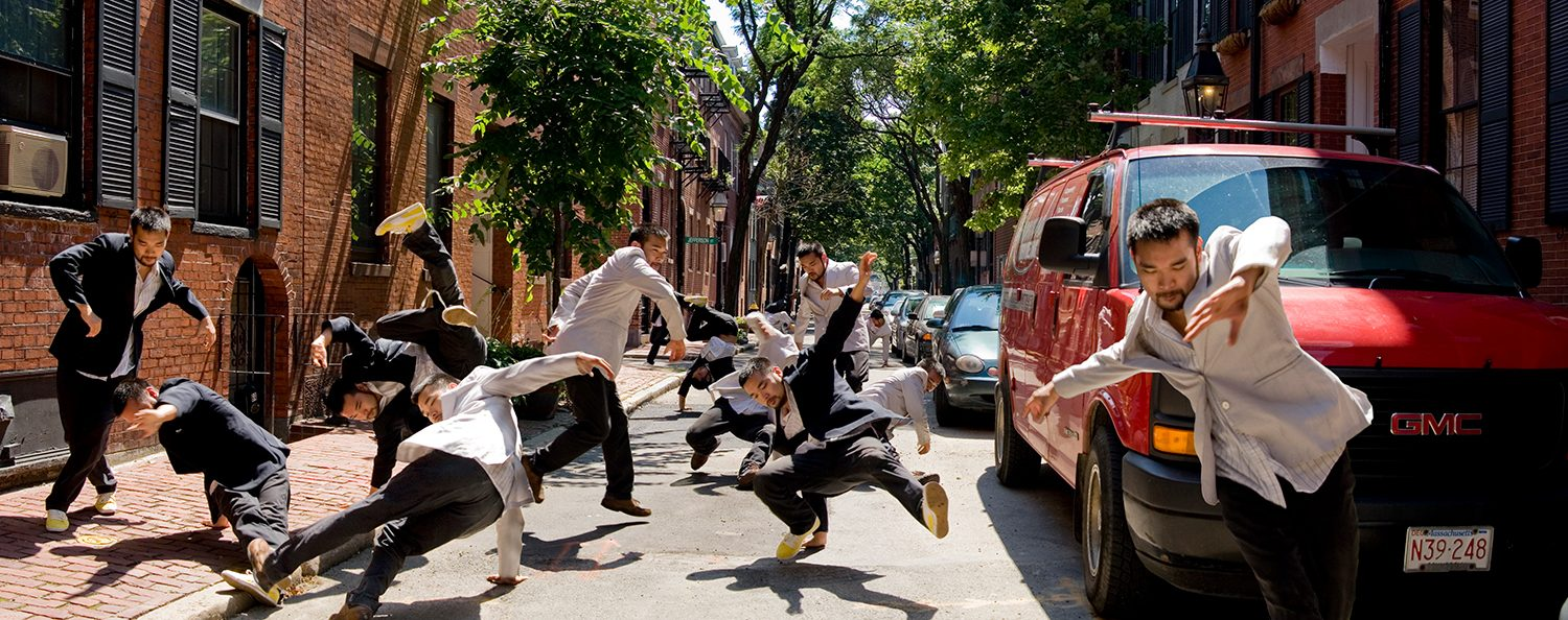 Battle - Two groups of asian guys in black and white suits break dancing on the street Boston's in Bay Village.